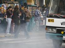 Imagen de archivo de unas personas cruzando una calle en Lima, jun 5, 2007. El Gobierno peruano aprobó el miércoles nuevos estándares ambientales más flexibles para las actividades extractivas, productivas y de servicios, alineándolos a los que adoptan otros países de la región como Chile y Colombia.  REUTERS/Enrique Castro-Mendivil (PERU)