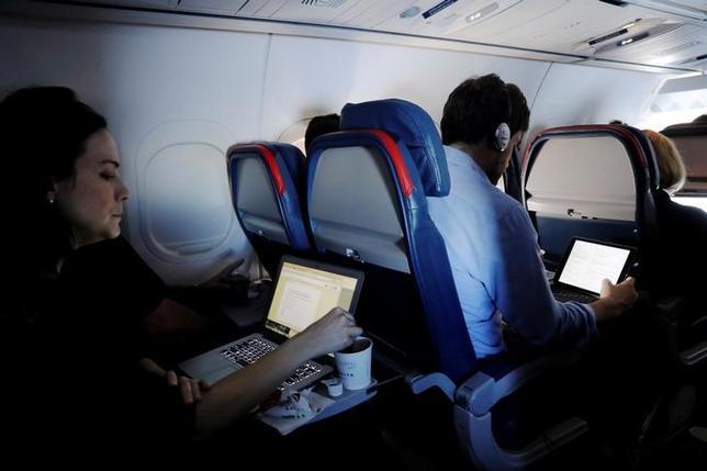 6月7日、米国のケリー国土安全保障省長官は、ラップトップなどの電子機器の航空機内持ち込み制限を拡大し、欧州、中東、アフリカの空港71カ所を対象とする考えを示唆した。ニューヨークのJFK国際空港から飛行機に乗った乗客ら、先月撮影(2017年 ロイター/Lucas Jackson)