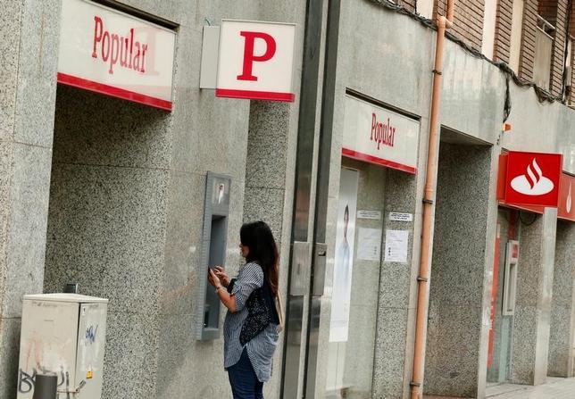 6月7日、EU規制当局者らは、資金繰りに行き詰まったスペイン銀バンコ・ポピュラールの救済に成功したことで、イタリアの地銀2行の救済に介入する根拠が強まったものの、同じ手法を使うことは難しいと考えている。写真は、バンコ・ポピュラールのATM。バルセロナで撮影(2017年 ロイター/Albert Gea)