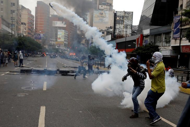 A demonstrator throws a tear gas canister during riots at a rally against Venezuelan president Nicolas Maduro's government in Caracas, Venezuela, June 7, 2017. REUTERS/Carlos Garcia Rawlins