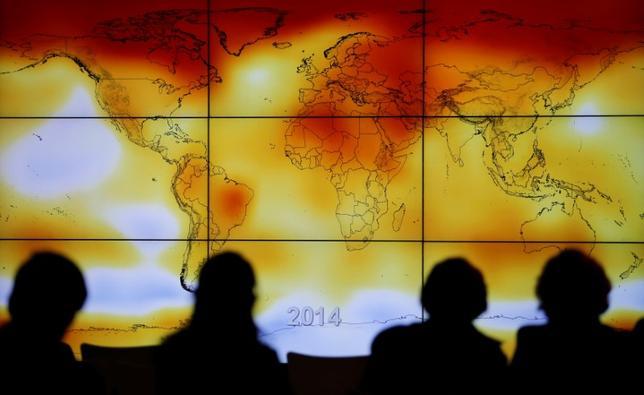6月8日、米カリフォルニア州政府と中国の清華大学は、米中気候変動研究所を設立し、地球温暖化を防ぐ技術の開発や研究で協力すると発表した。写真は画面に映し出された異常気象の様子を見るCOP21の参加者たち。2015年12月撮影(2017年 ロイター/Stephane Mahe)