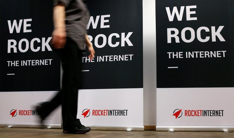 FILE PHOTO: A woman walks past a banner at the shareholder meeting of Rocket Internet, a German venture capital group in Berlin, Germany, June 23, 2015. REUTERS/Fabrizio Bensch/File Photo
