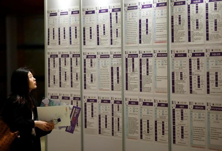 FILE PHOTO: A woman looks at recruiting information during a job fair in Seoul, South Korea, April 12, 2017.  REUTERS/Kim Hong-Ji