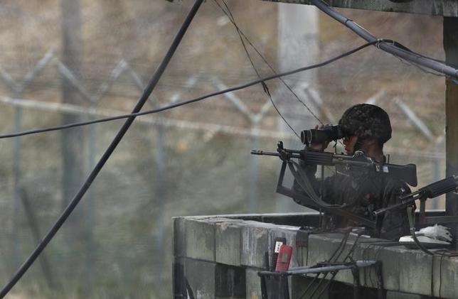 6月9日、韓国軍は、北朝鮮との南北軍事境界線に近い山間部で小型の飛行体を発見したと明らかにした。写真は韓国と北朝鮮を分ける非武装地帯(DMZ)近くの観測所で、双眼鏡で北方をみる韓国軍兵士。韓国パジュで2013年4月撮影(2017年 ロイター/Kim Hong-Ji)