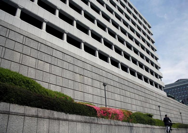 FILE PHOTO: A man riding a bicycle rides past the Bank of Japan building in Tokyo, Japan April 27, 2017. REUTERS/Kim Kyung-Hoon