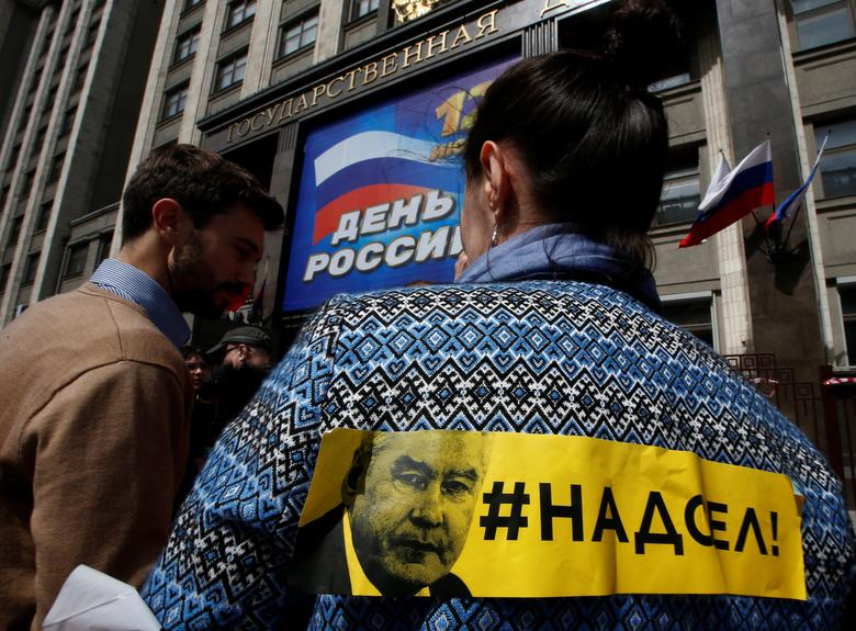 A woman has a sticker with #tiredofhim slogan and depicting Moscow's Mayor Sergei Sobyanin during a picket against a renovation law under the Moscow government's renovation plan in front of the State Duma, the lower house of parliament, in Moscow, Russia, June 9, 2017. REUTERS/Sergei Karpukhin