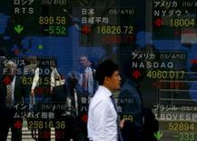 Un hombre camina cerca de una muestra del promedio Nikkei y otros índices de mercado, fuera de una correduría en Tokio. 19 de abril 2016.  El índice Nikkei de la bolsa de Tokio subió el viernes luego de que las acciones de SoftBank repuntaron más de un 7 por ciento, pero los operadores dijeron que un resultado sorpresivo en las elecciones de Reino Unido agitó a los inversores. REUTERS/Thomas Peter
