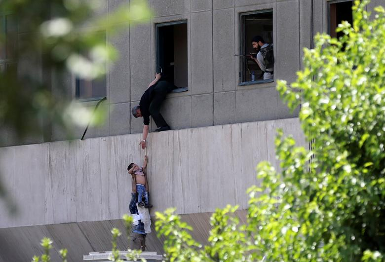 A boy is evacuated during an attack on the Iranian parliament in central Tehran. Omid Vahabzadeh/TIMA via REUTERS