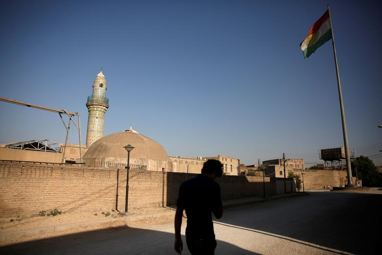 A man makes his way as a Kurdish flag flutters atop the Citadel of Erbil, northern Iraq June 8, 2017. REUTERS/Alkis Konstantinidis