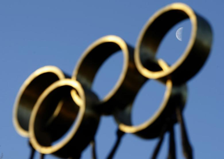 The moon is pictured through a sculpture in front of the International Olympic Committee (IOC) headquarters in Lausanne December 9, 2009. REUTERS/Denis Balibouse/Files