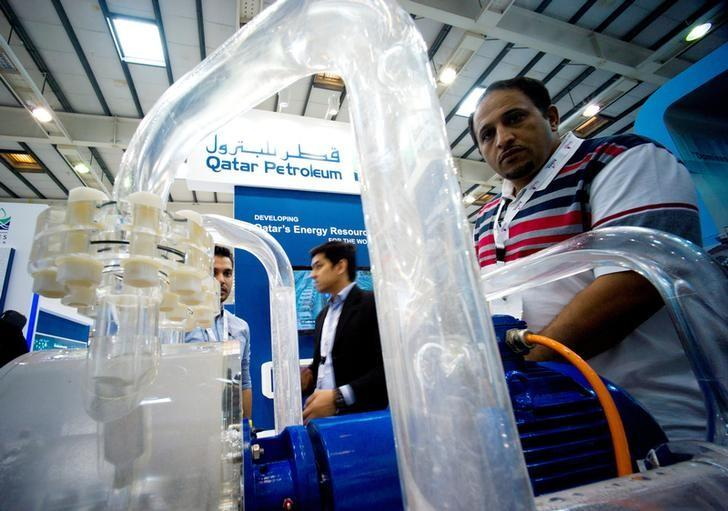 Visitors look at an oil purification unit at a petrochemicals conference in Manama, Bahrain May 19, 2014. REUTERS/Hamad I Mohammed/Files