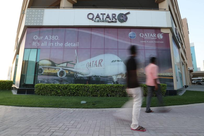 People walk past the Qatar Airways office in Manama, Bahrain, June 8, 2017. Picture taken June 8, 2017. REUTERS/Hamad I Mohammed