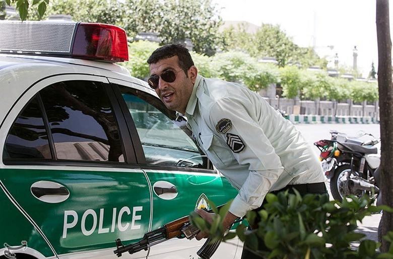 An Iranian policeman takes cover during an attack on the Iranian parliament in central Tehran, Iran. Tasnim News Agency/Handout via REUTERS
