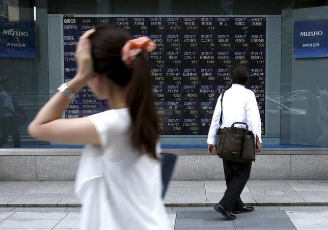 6月12日、寄り付きの東京株式市場で、日経平均は前日比92円49銭安の1万9920円77銭となり反落して始まった。写真は株価ボードを眺める男性、都内で2015年6月撮影(2017年 ロイター/Issei Kato)