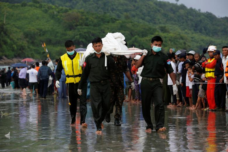 Military soldiers carry dead bodies from a crashed military plane outside Launglon township, Myanmar. REUTERS/Soe Zeya Tun
