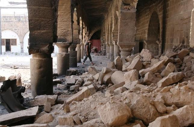 6月12日、シリア政権軍とイランが支援する民兵組織が、シリア南部ダルアーの反体制派が支配する地域への攻撃を強化している。写真は空爆により破壊されたモスクで瓦礫の間を歩く男性。ダルアーで9日撮影(2017年 ロイター/ALAA AL-FAQIR)
