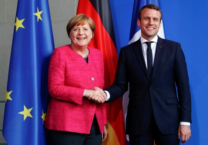 FILE PHOTO: German Chancellor Angela Merkel and French President Emmanuel Macron shake hands after a news conference at the Chancellery in Berlin, Germany, May 15, 2017.   REUTERS/Fabrizio Bensch/Files