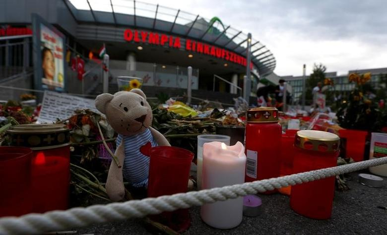 FILE PHOTO: Candles and flowers are laid in front of the Olympia shopping mall in Munich, Germany July 31, 2016. REUTERS/Michaela Rehle