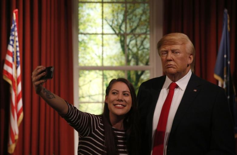 A woman poses with a waxwork of U.S. President-elect Donald Trump during a media event at Madame Tussauds  in London, Britain January 18, 2017. REUTERS/Neil Hall