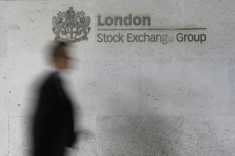 FILE PHOTO: A man walks past the London Stock Exchange in the City of London October 11, 2013.  REUTERS/Stefan Wermuth