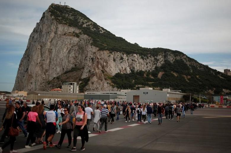 Pedestrians cross the tarmac at Gibraltar International Airport in front of the Rock of Gibraltar, near the border with Spain, in the British overseas territory of Gibraltar, historically claimed by Spain, April 27, 2017. REUTERS/Jon Nazca