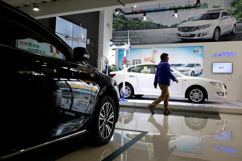 File Photo: A Man Walks Through An Electric Car Dealership In Shanghai, China, January 11, 2017. Reuters/Aly Song/File Photo