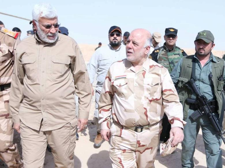 Iraqi Prime Minister Haider al-Abadi (C) walks with Abu Mahdi al-Muhandis, (L), the deputy commander of the Popular Mobilization Forces (PMF) during his visit to Mosul, Iraq May 29, 2017. Iraqi Prime Minister Office/Handout via REUTERS