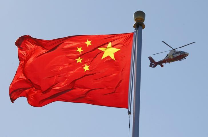 FILE PHOTO - A helicopter flies over the Chinese national flag in Tiananmen Square October 9, 2012. REUTERS/David Gray