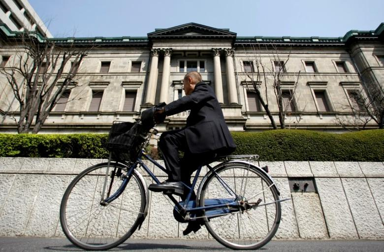 A man rides a bicycle past the Bank of Japan (BOJ) building in Tokyo, Japan March 18, 2009. REUTERS/Yuriko Nakao/Files