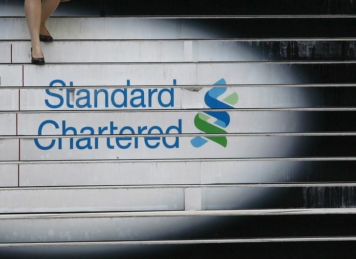 FILE PHOTO -  A woman walks down the stairs of the Standard Chartered headquarters in Hong Kong in this October 13, 2010 file photo. REUTERS/Bobby Yip/File Photo