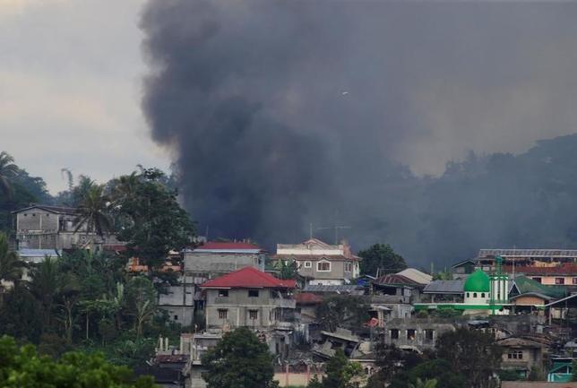 6月14日、フィリピン軍報道官は、同軍が過激派組織「イスラム国」(IS)系武装勢力の掃討作戦を実施している南部ミンダナオ島のマラウィ市付近で、米軍がフィリピン軍の支援活動を行っていることを明らかにした。写真は爆撃を受け黒煙が上がるマラウィ市街。13日撮影(2017年 ロイター/Romeo Ranoco)
