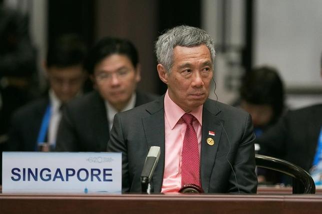 6月14日、シンガポールのリー・シェンロン首相の弟と妹が、兄への信頼を失ったとする声明を発表した。首相の妹にあたるリー・ウェイリン氏と弟のリー・シェンヤン氏は「政府機関がわれわれに対して動いている」との懸念を表明。写真は昨年9月中国の杭州で行われたG20に参加する同首相(2017年 ロイター)