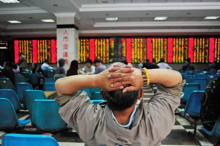 An investor looks at an electronic board showing stock information at a brokerage house in Nanjing, China May 24, 2017. REUTERS/Stringer/Files