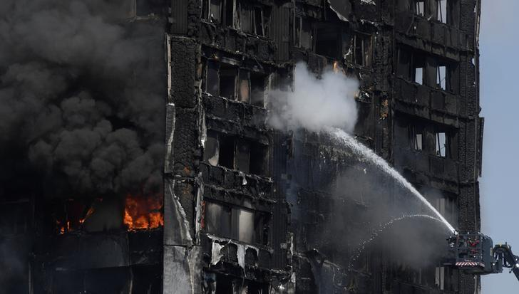 Firefighters direct jets of water onto a tower block severely damaged by a serious fire, in north Kensington, West London, Britain June 14, 2017. REUTERS/Toby Melville