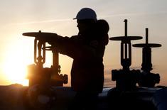 Imagen de archivo en la que un operario comprueba una válvula en una instalación petrolera de Lukoil cerca de Kogalym, Rusia, el 25 de enero de 2016. La Agencia Internacional de Energía (AIE) espera que el crecimiento de la oferta de petróleo el próximo año supere un incremento previsto de la demanda que impulsaría el consumo mundial sobre los 100 millones de barriles por día (bpd) por primera vez, dijo el organismo el miércoles. REUTERS/Sergei Karpukhin