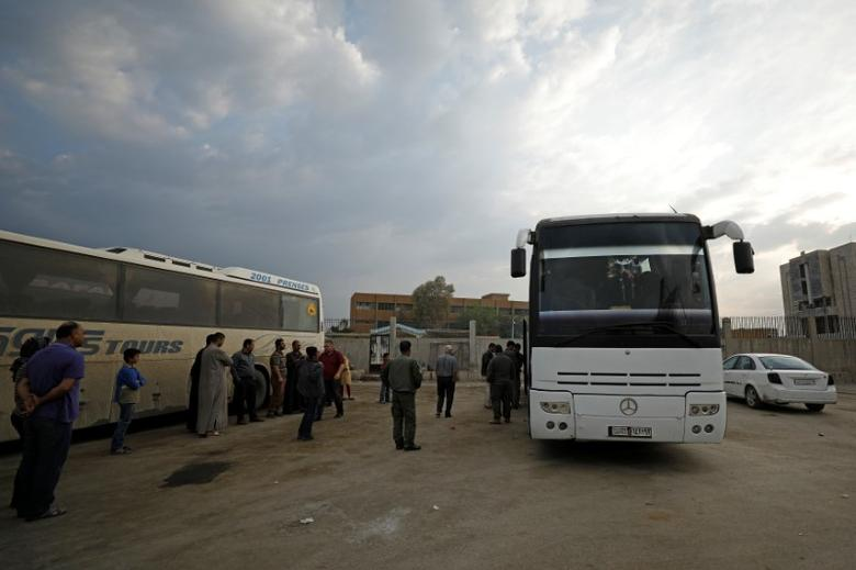 Passengers wait in Qamishli city in Syria's Kurdish-held northeast to embark on a bus headed for government-controlled Aleppo, Syria May 7, 2017. Picture taken May 7, 2017. REUTERS/Rodi Said