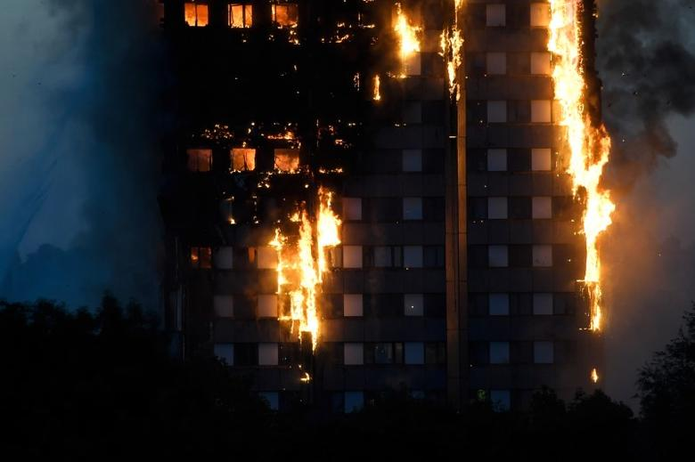 Flames and smoke billow as firefighters deal with a serious fire in a tower block at Latimer Road in West London. REUTERS/Toby Melville