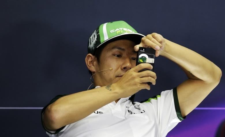 Caterham Formula One driver Kamui Kobayashi of Japan takes a picture during a news conference at the Hungaroring circuit, near Budapest in this file photo dated July 24, 2014.  REUTERS/David W Cerny