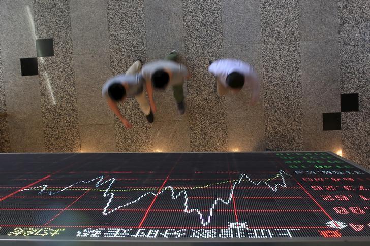资料图片:2015年9月,上海陆家嘴金融区,人们经过上交所一处股票信息显示屏。REUTERS/Aly Song