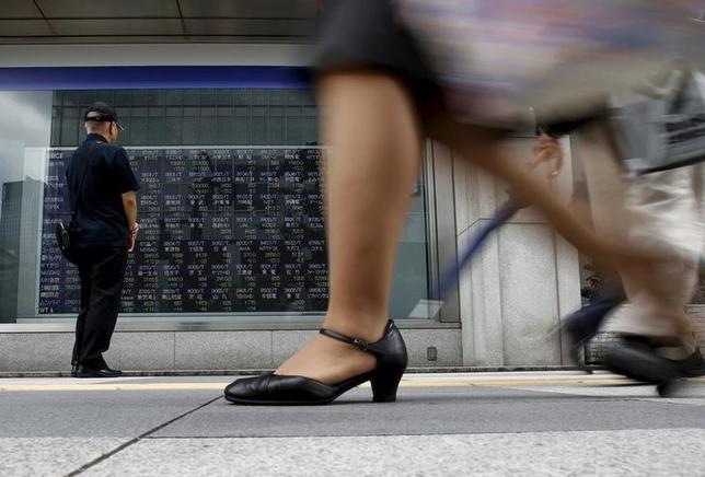 6月15日、前場の東京株式市場で、日経平均株価は前営業日比86円06銭安の1万9797円46銭となり、4日続落した。写真は株価ボードを眺める男性、2015年8月撮影(2017年 ロイター/Yuya Shino)