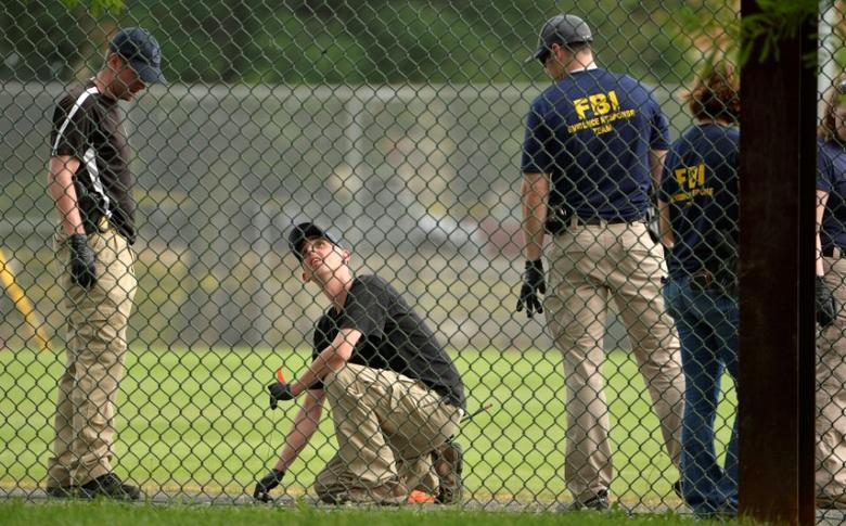 FBI technicians examine the outfield area of a baseball field for evidence where shots were fired during a Congressional baseball practice wounding House Majority Whip Steve Scalise (R-LA), in Alexandria, Virginia, U.S., June 14, 2017.   REUTERS/Mike Theiler