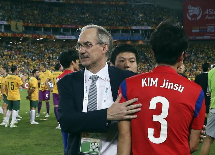 South Korea's coach Uli Stielike consoles player Kim Jin-su (R) after their Asian Cup final soccer match against Australia at the Stadium Australia in Sydney January 31, 2015. REUTERS/Steve Christo/Files