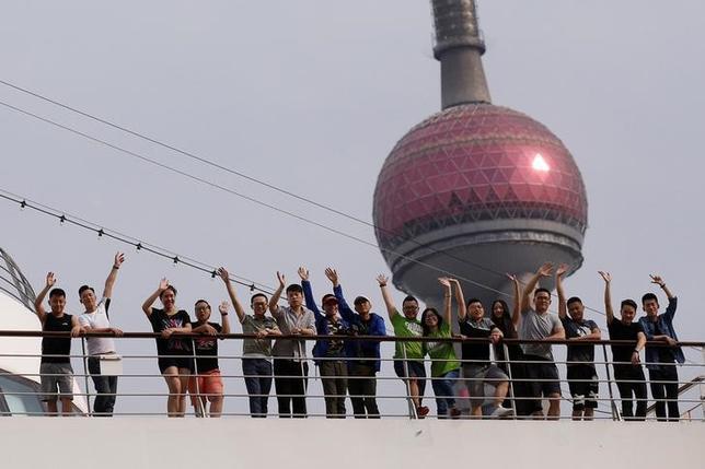6月14日、中国で1週間にわたって行われている性的少数者(LGBT)の啓発イベント「プライド」に合わせ、中国から日本に出航したクルーズ船上で、LGBTカップルが結婚式を挙げる。写真は上海の港で船から手をふるカップルら(2017年 ロイター/Aly Song)