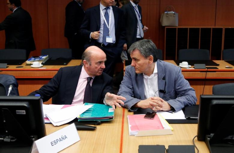 Spain's Economy Minister Luis de Guindos and Greek Finance Minister Euclid Tsakalotos (R) attend a eurozone finance ministers meeting in Brussels, Belgium May 22, 2017. REUTERS/Francois Lenoir