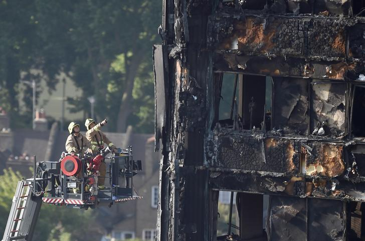 Firefighters use a hydraulic lift to inspect the Grenfell Tower block that was destroyed by fire, in north Kensington, West London, Britain June 16, 2017. REUTERS/Hannah McKay