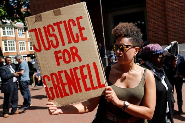 A demonstrator holds a banner at Kensington Town Hall, following the fire that destroyed The Grenfell Tower block, in north Kensington, West London, Britain June 16, 2017. REUTERS/Stefan Wermuth