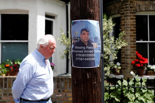 A man walks by a missing person poster near The Grenfell Tower block, destroyed by fire, in north Kensington, West London, Britain June 16, 2017. REUTERS/Stefan Wermuth