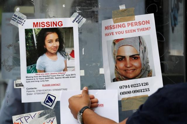 A woman touches missing person posters near The Grenfell Tower block, destroyed by fire, in north Kensington, West London, Britain June 16, 2017. REUTERS/Stefan Wermuth