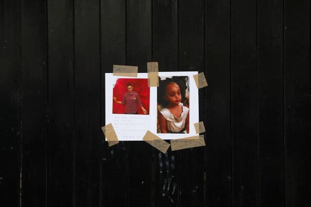 Missing person photographs are attached to a fence near The Grenfell Tower block, destroyed by fire, in north Kensington, West London, Britain June 16, 2017. REUTERS/Stefan Wermuth