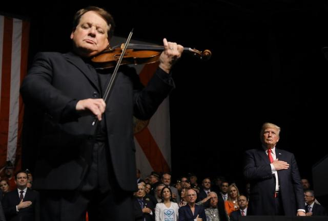 U.S. President Donald Trump listens to Cuban violinist Luis Haza play the US National Anthem after Trump spoke about US-Cuba relations at the Manuel Artime Theater in Miami, Florida, U.S., June 16, 2017. REUTERS/Carlos Barria